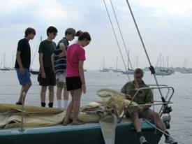 Prout sailors watch Coach Cooper working on the Bow of Jaded, a  J 105