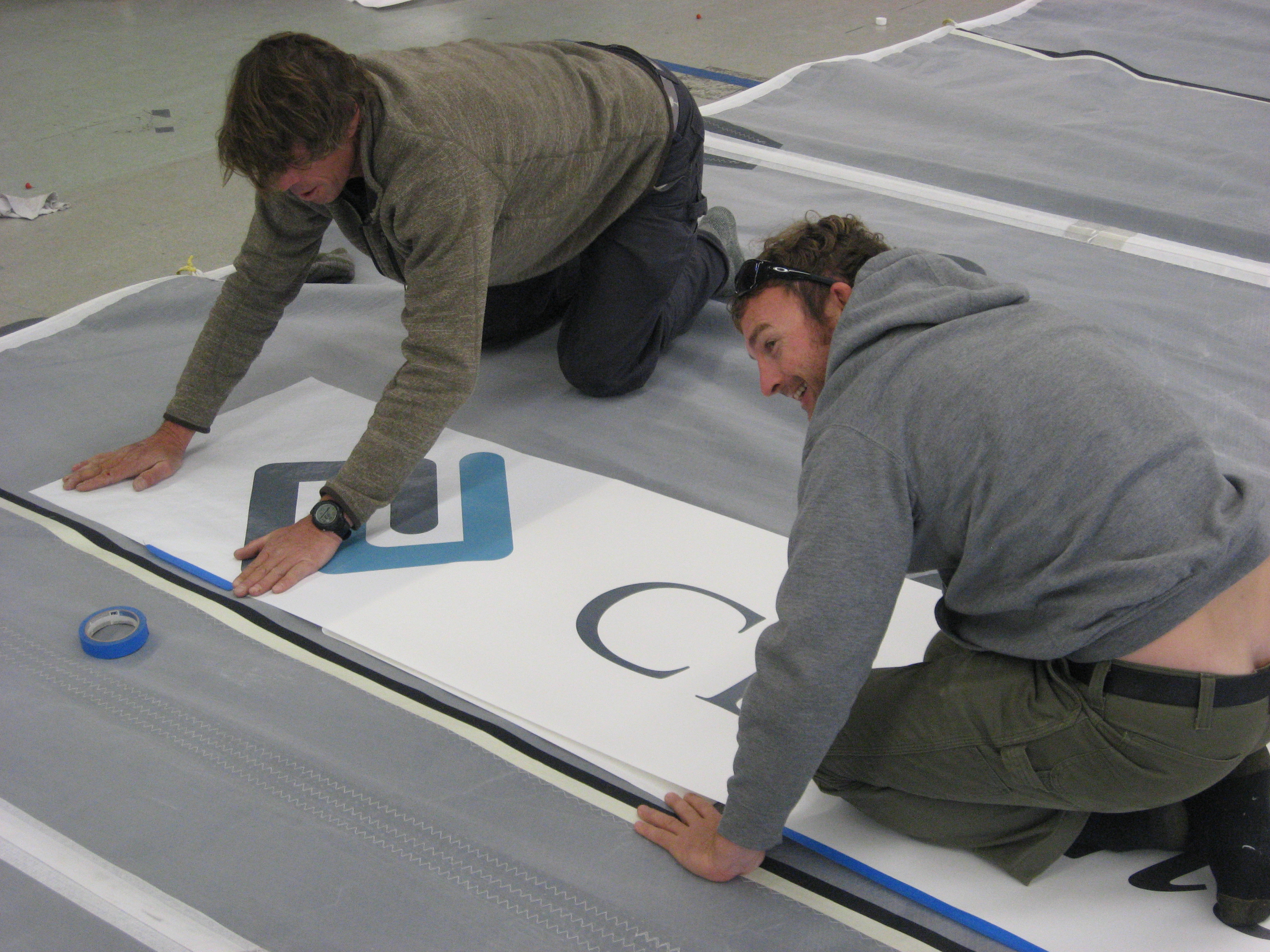 Rob Windsor, left and Hugh Piggin applying the logo for CBL insurance  of NZL to Joe Harris's mainsail.